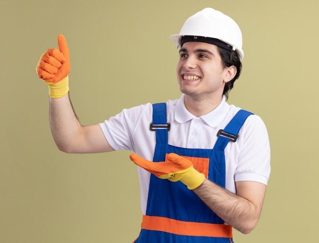 緑の壁の上に元気に立って笑顔を見せて脇を見ているゴム手袋の建設制服と安全ヘルメットの若いビルダー男