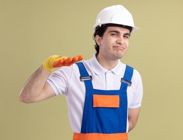 Молодой строитель в строительной форме и защитном шлеме в резиновых перчатках смотрит вперед, делая жест успокоения с рукой, стоящей над зеленой стеной