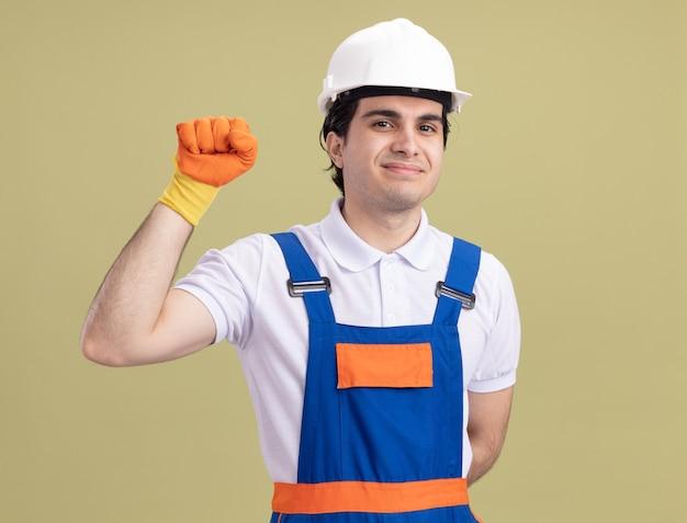 緑の壁の上に立って自信を持って上げている握りこぶしを笑顔で正面を見てゴム手袋の建設制服と安全ヘルメットの若いビルダー男