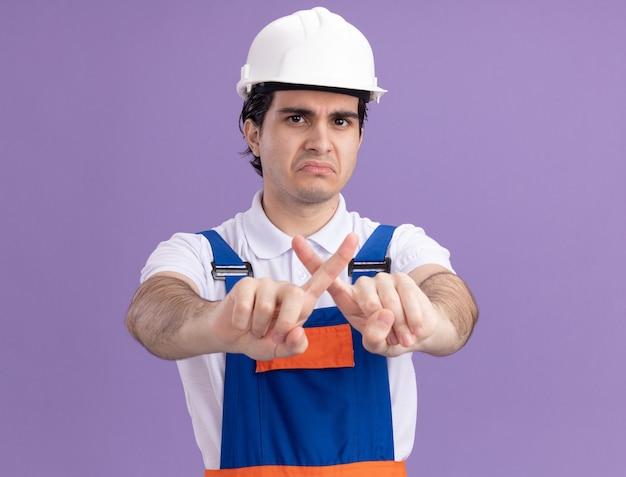 建設制服と安全ヘルメットの若いビルダーの男は、紫色の壁の上に立っている人差し指を横切って停止ジェスチャーを作る深刻な顔で正面を向いています