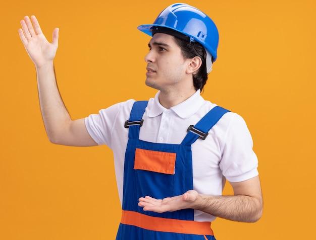 オレンジ色の壁の上に立っている手で身振りで示すことに不満を脇に見ている建設制服と安全ヘルメットの若いビルダー男