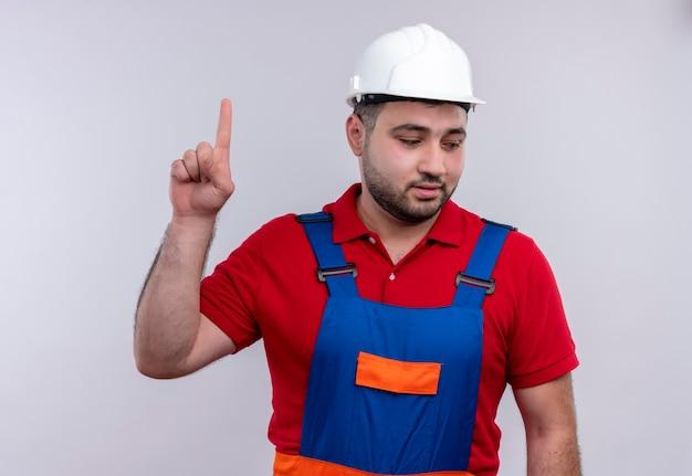 Молодой строитель в строительной форме и защитном шлеме смотрит в сторону, улыбаясь, указывая указательным пальцем вверх