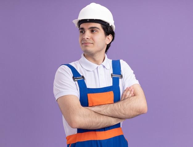 Молодой строитель в строительной форме и защитном шлеме, уверенно глядя в сторону со скрещенными руками, стоит над фиолетовой стеной