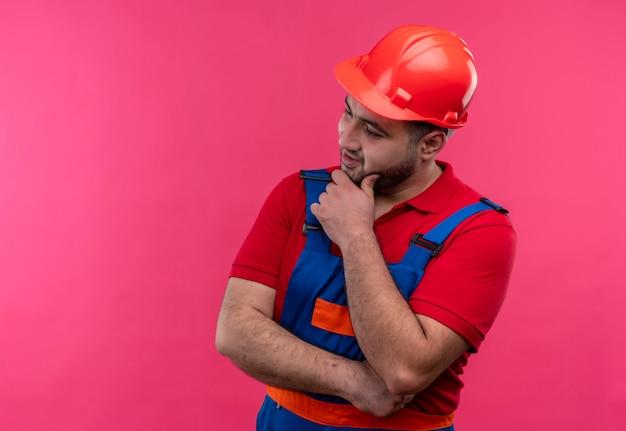 建設制服と安全ヘルメットの若いビルダー男は、顔に物思いにふける表情で顎に手を脇に見ています