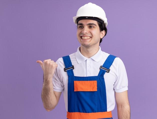 Молодой строитель в строительной форме и защитном шлеме смотрит в сторону с улыбкой на лице, указывая на сторону, стоящую над фиолетовой стеной