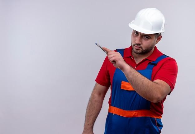 建設制服と安全ヘルメットの若いビルダーの男がカメラを見て不機嫌にペンで横を指しています