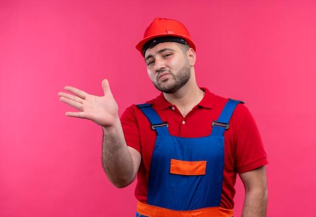 건설 유니폼 및 안전 헬멧에 젊은 작성기 남자 손으로 몸짓 미소 카메라를보고