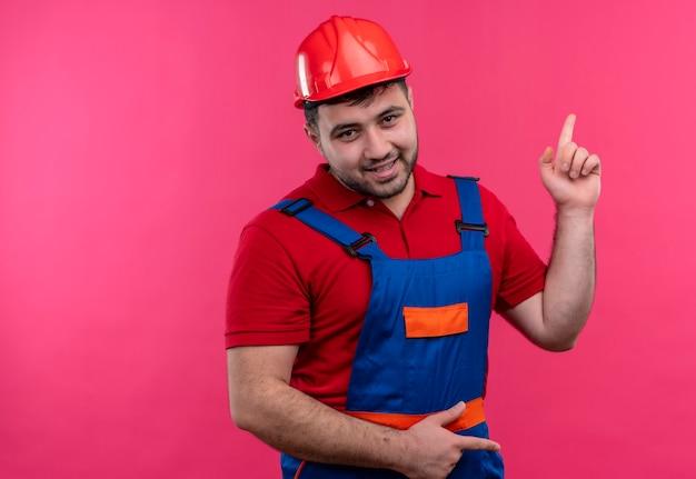 後ろの何かを指している自信を持って笑顔でカメラを見て建設制服と安全ヘルメットの若いビルダー男