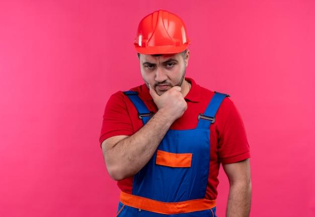 物思いにふける表情で顎に手で眉をひそめている顔でカメラを見て建設制服と安全ヘルメットの若いビルダー男
