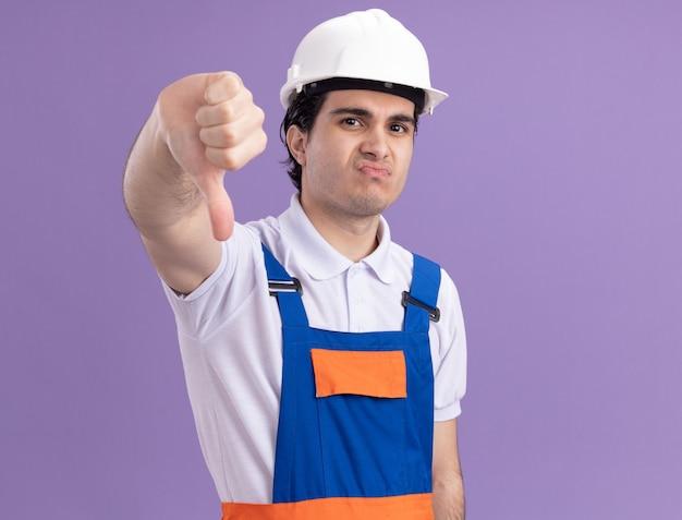 Молодой строитель в строительной форме и защитном шлеме, недовольно глядя на фронт, показывает большие пальцы вниз, стоя над фиолетовой стеной