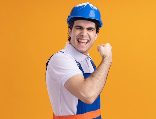 Молодой строитель в строительной форме и защитном шлеме, глядя на фронт счастливым и возбужденным сжимающим кулак, стоящим над оранжевой стеной