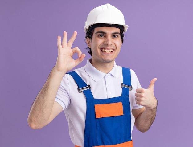 건설 유니폼과 안전 헬멧에 젊은 작성기 남자는 행복하고 긍정적 인 보여주는 확인 서명과 보라색 벽 위에 서 엄지 손가락을보고