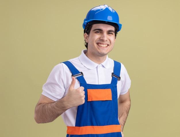 Молодой строитель в строительной форме и защитном шлеме смотрит вперед, весело улыбаясь, показывает палец вверх, стоя над зеленой стеной