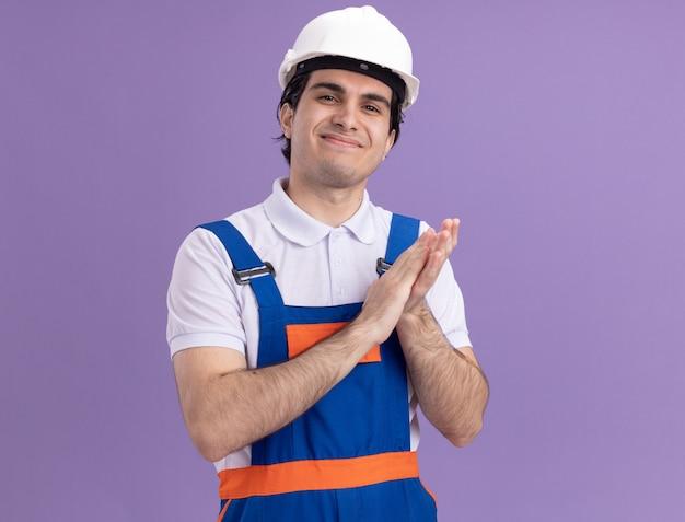 Молодой строитель в строительной форме и защитном шлеме, глядя вперед, улыбаясь, уверенно аплодируя, стоя над фиолетовой стеной
