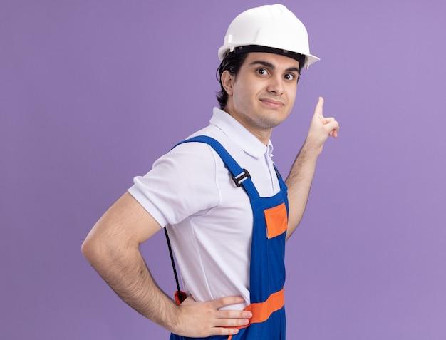 Молодой строитель в строительной форме и защитном шлеме, глядя вперед, улыбается, уверенно указывая указательным пальцем на что-то, стоящее над фиолетовой стеной