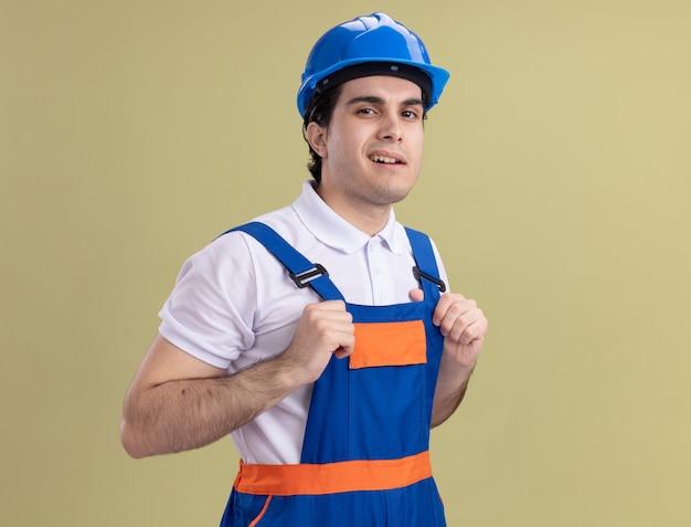 Молодой строитель в строительной форме и защитном шлеме, глядя на фронт, уверенно улыбаясь, стоит над зеленой стеной