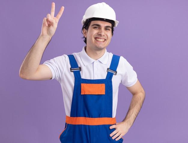 Молодой строитель в строительной форме и защитном шлеме смотрит вперед, улыбаясь счастливым лицом, показывая v-знак, стоящий над фиолетовой стеной