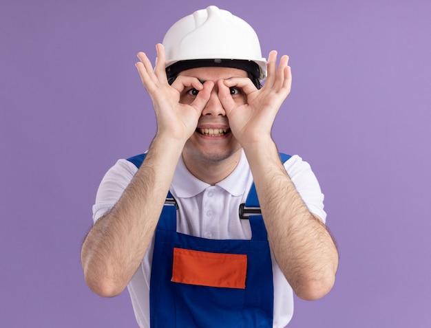 Молодой строитель в строительной форме и защитном шлеме, смотрящий в лицо сквозь пальцы, делая бинокулярный жест, улыбаясь, стоя над фиолетовой стеной