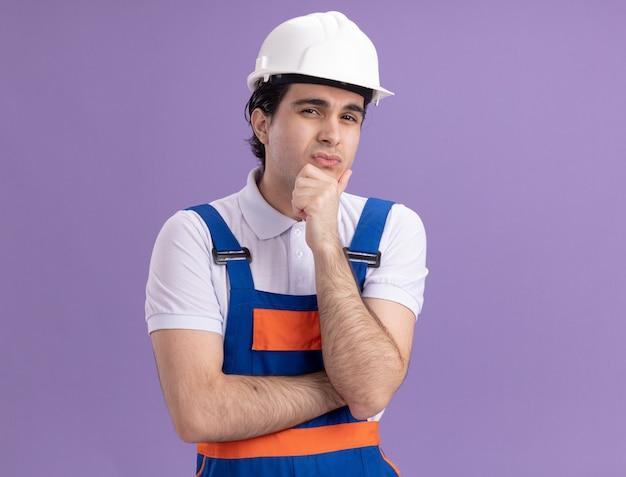 紫色の壁の上に立っていると考えて彼のあごに手で正面を見て建設制服と安全ヘルメットの若いビルダー男
