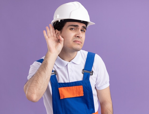 건설 유니폼과 안전 헬멧에 젊은 작성기 남자는 보라색 벽 위에 서있는 수군을 듣고 그의 귀에 손으로 정면을보고