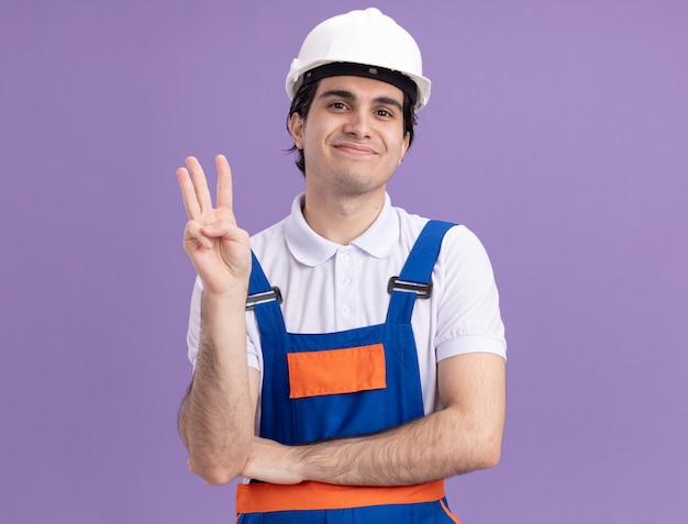 건설 유니폼 및 안전 헬멧에 젊은 작성기 남자 보라색 벽 위에 서있는 세 번째를 보여주는 얼굴에 미소로 정면을보고