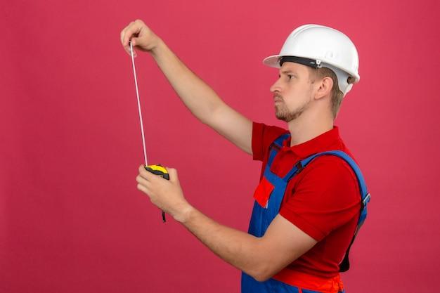 孤立したピンクの壁に彼の手で物思いに沈んだ表情で測定テープを見て建設制服と安全ヘルメットの若いビルダー男