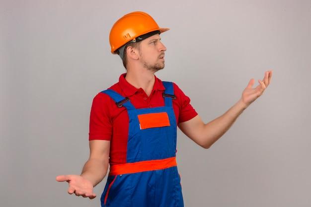 Молодой строитель человек в строительной форме и защитный шлем, глядя в сторону, делая запутанный жест с руками и выражением, как задающий вопрос над изолированной белой стеной