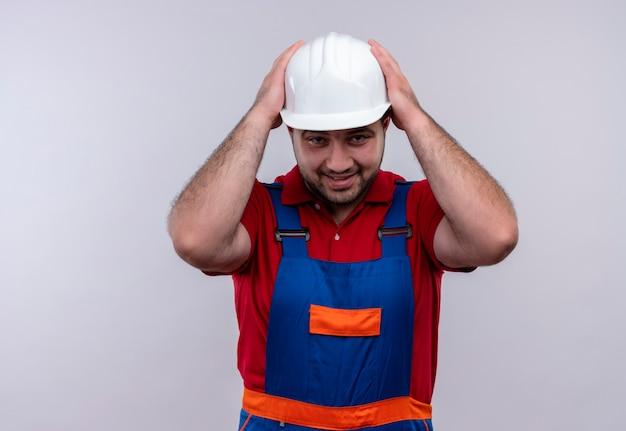 彼の頭に失望し、混乱しているように見える建設制服と安全ヘルメットの若いビルダー男