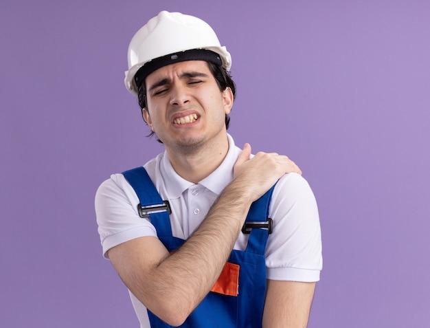 紫色の壁の上に立っている痛みを感じて彼の肩に触れて気分が悪いように見える建設制服と安全ヘルメットの若いビルダー男