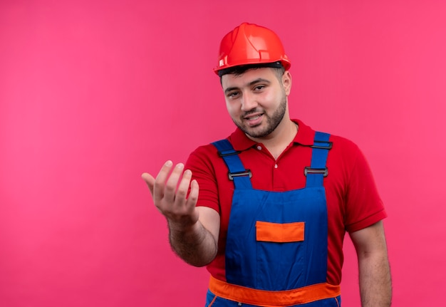 Молодой строитель в строительной униформе и защитном шлеме делает жест и дружелюбно улыбается рукой