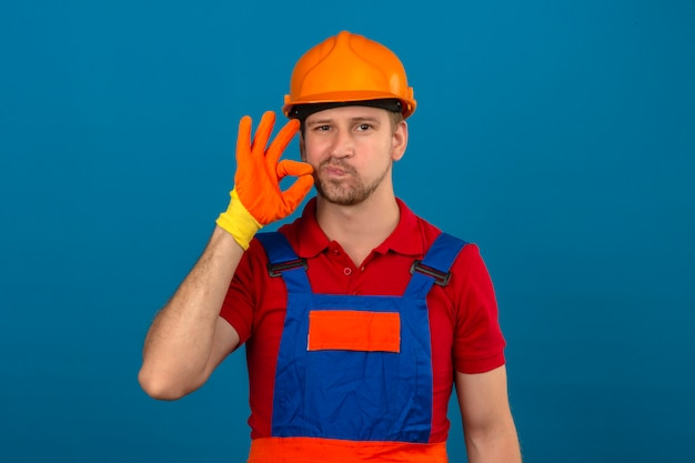 Молодой строитель человек в строительной форме и защитный шлем, делая жест молчания, как будто закрыв рот молнией над синей стеной