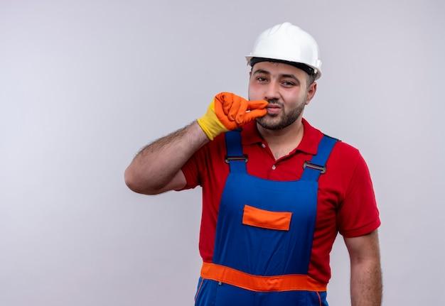 지퍼로 입을 닫는 것과 같은 침묵 제스처를 만드는 건설 유니폼 및 안전 헬멧에 젊은 작성기 남자