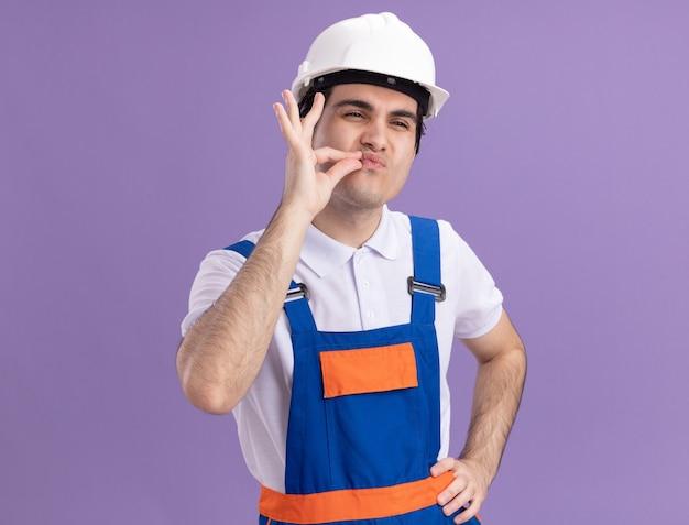 보라색 벽 위에 서있는 지퍼로 입을 닫는 것과 같은 손가락으로 침묵 제스처를 만드는 건설 유니폼 및 안전 헬멧에 젊은 작성기 남자