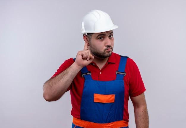 建設制服と安全ヘルメットの若いビルダーの男が耳を傾けようとしている彼の耳を指しています