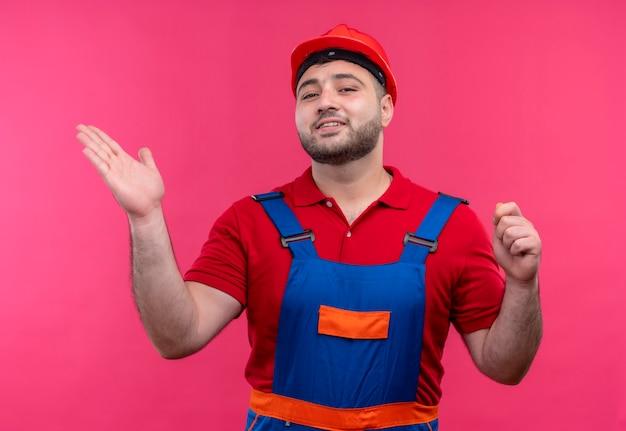Молодой строитель в строительной форме и защитном шлеме, указывая рукой в сторону, уверенно улыбаясь
