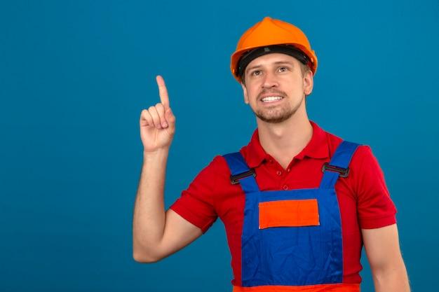 Молодой строитель человек в строительной форме и защитный шлем, указывая пальцем вверх с улыбкой на лице лицо над синей стеной