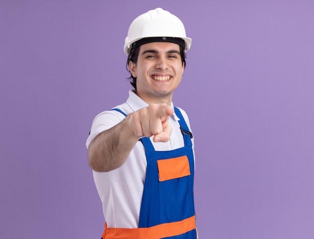 紫色の壁の上に元気に立って笑顔の前に人差し指で指している建設制服と安全ヘルメットの若いビルダー男