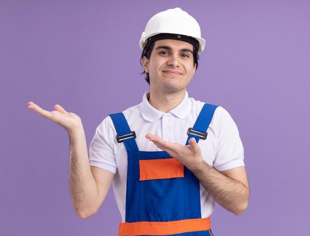 Молодой строитель в строительной форме и защитном шлеме, представляя пространство для копирования с руками, весело улыбаясь, стоя над фиолетовой стеной