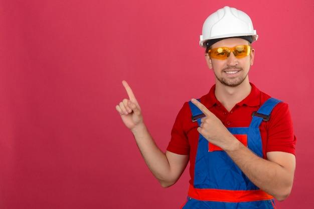 笑みを浮かべて、コピースペースで孤立したピンクの壁を越えて2つの手と指で側を指しているカメラを見て建設制服と安全ヘルメットの若いビルダー男