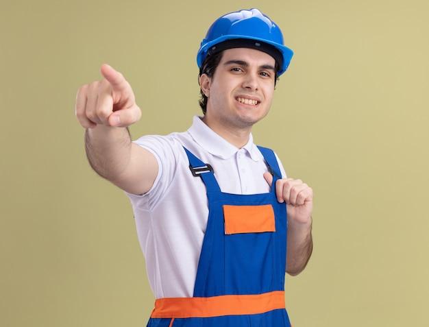 Молодой строитель в строительной форме и защитном шлеме, уверенно улыбаясь, указывая указательным пальцем вперед, улыбаясь, стоя над зеленой стеной