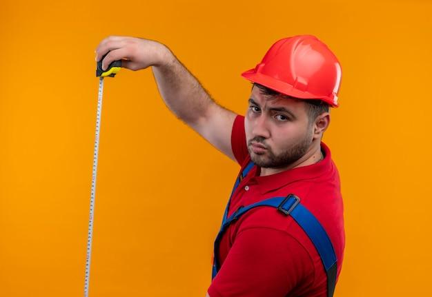 심각한 얼굴로 카메라를보고 측정 테이프를 사용하여 건설 유니폼 및 안전 헬멧에 젊은 작성기 남자