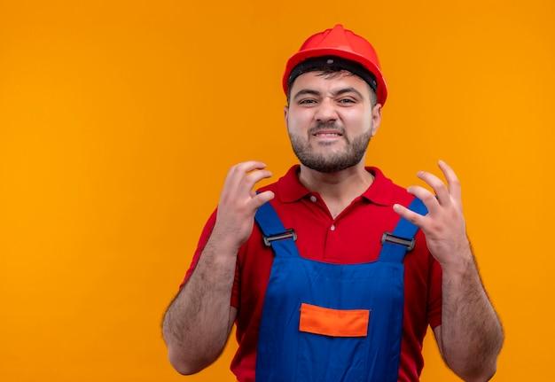 건설 유니폼과 안전 헬멧에 젊은 작성기 남자는 매우 화가 좌절하고 팔을 올리는 스트레스