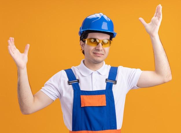 건설 유니폼 및 안전 헬멧에 젊은 작성기 남자 오렌지 벽 위에 서 제기 팔으로 전면 행복하고 긍정적 인 찾고 안경을 착용