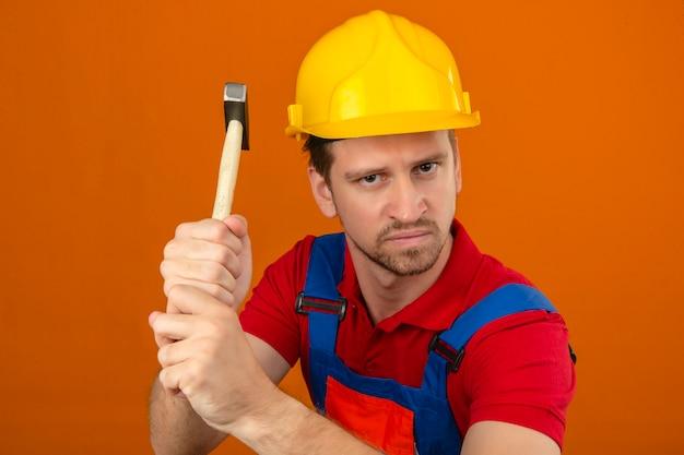 격리 된 오렌지 벽에 망치로 공격 위협 화가 건설 유니폼과 안전 헬멧에 젊은 작성기 남자