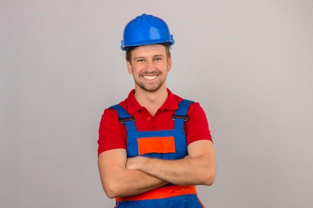 Молодой строитель в униформе и защитной каске с уверенной улыбкой на лице и скрещенными руками на изолированной белой стене