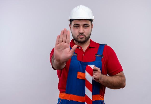 建設ユニフォームと深刻な顔で一時停止の標識を作る開いた手で安全ヘルメットの若いビルダー男