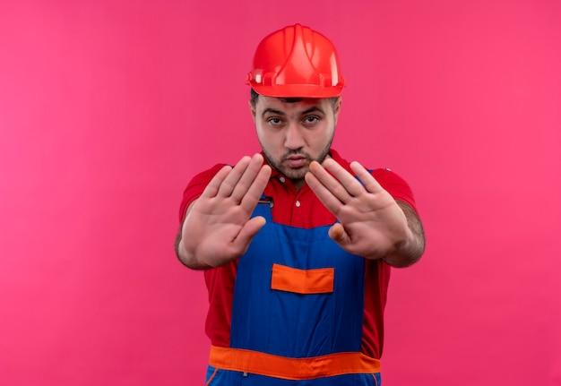 Молодой строитель в строительной форме и защитном шлеме с открытыми руками делает знак остановки с серьезным лицом