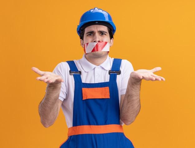 オレンジ色の壁の上に立っている混乱した肩をすくめる肩を見て口の周りにテープを巻いた建設制服と安全ヘルメットの若いビルダー男