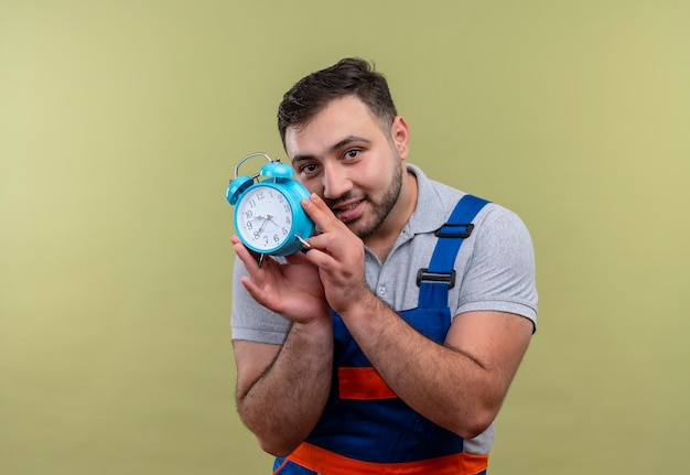 Молодой строитель человек в строительной форме держит будильник, хитро глядя в камеру