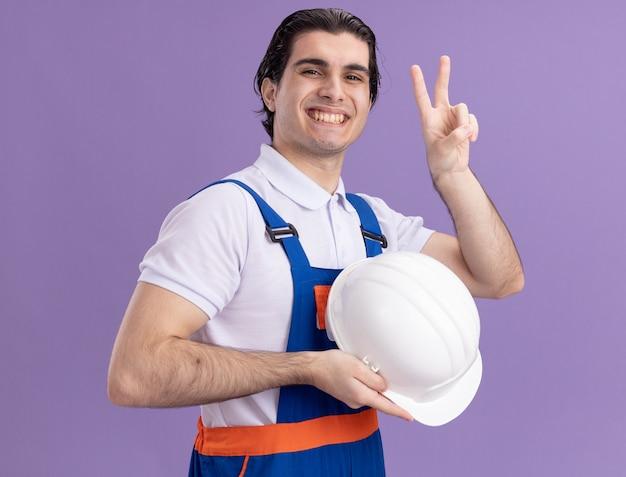 Молодой строитель в строительной форме держит свой защитный шлем, глядя вперед с уверенной улыбкой, показывая v-знак, стоящий над фиолетовой стеной